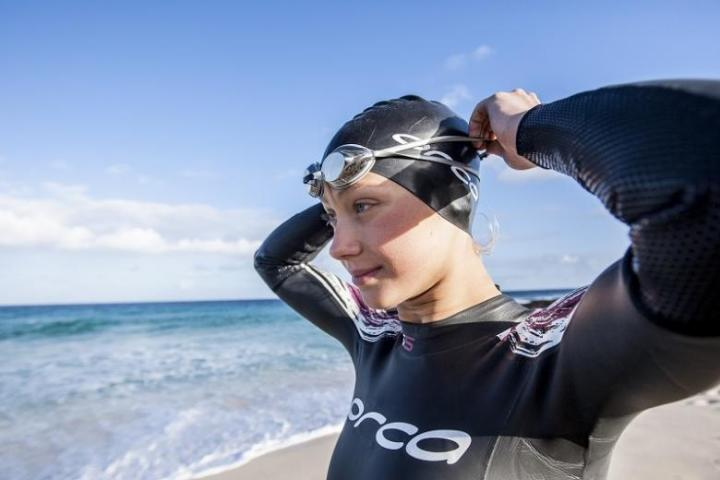 A woman preparing for a swim in Orca kit