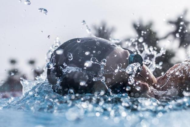A swimmer in action wearing an Orca swimming cap