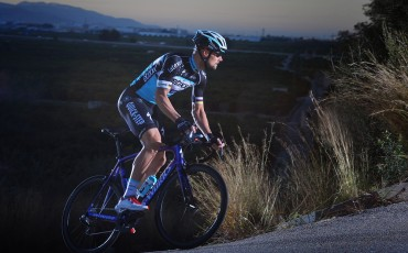 Etixx sponsored road rider climbing up a hill at dusk