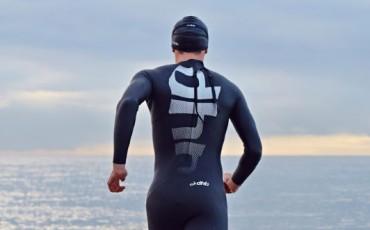 Imagen de un nadador con el neopreno dhb corriendo hacia la orilla