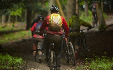 camera shot following a group of mountain bikers riding in muddy conditions