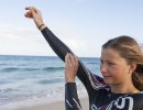 A woman adjusting her Orca wetsuit by the sea